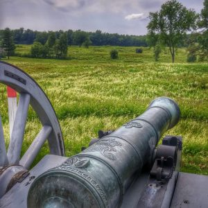 Revolutionary war erra muffle style cannon on wheels aimed towards the field. This is the area where the Battle of Saratoga, the turning point in the Revolutionary War, was won against the British Army.